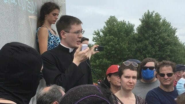 Priest pleads with mob not to attack saint's statue. They tell him they're coming for cathedral next.